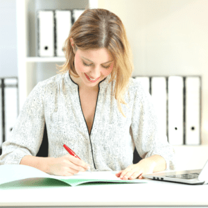 A woman smiling and writing