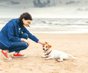 A woman with her dog on the beach